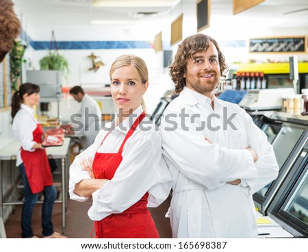 Portrait of happy butchers with arms crossed standing together in store - stock photo