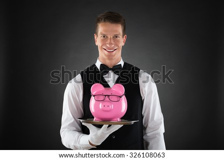 Portrait Of Happy Butler Holding Tray With Pink Piggybank - stock photo