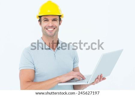 Portrait of happy carpenter using laptop over white background - stock photo