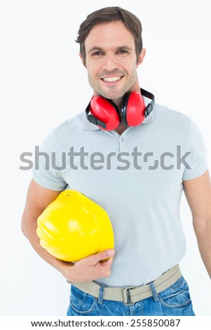 Portrait of happy carpenter with hard hat and ear protectors over white background - stock photo