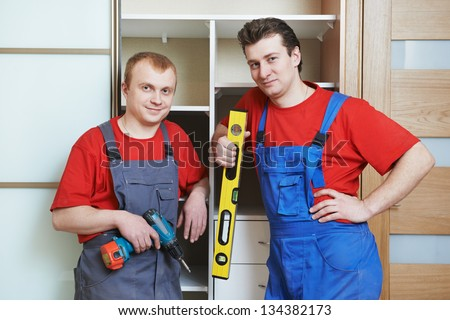 Portrait of happy carpenter worker team in front of home built-in cupboard - stock photo