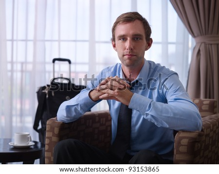 Portrait of happy caucasian businessman with crossed fingers smiling at camera in hotel room during business trip. Front view - stock photo