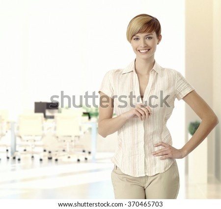 Portrait of happy caucasian casual blonde young business office manager. Standing, smiling, looking at camera, hand on hip, copyspace. - stock photo