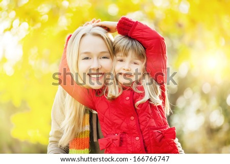Portrait of happy,caucasian sisters smiling and hugging outdoors. Shallow doff and lens flare - stock photo