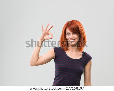 portrait of happy caucasian woman showing ok sign, against grey background - stock photo