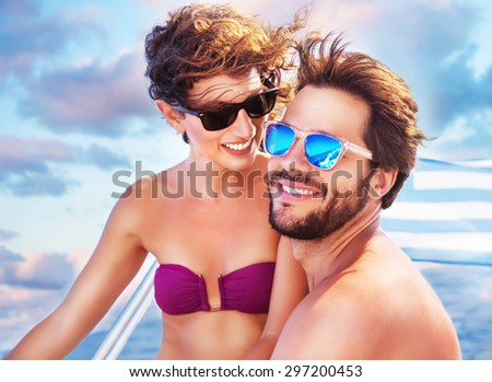 Portrait of happy cheerful cute couple having fun on sailboat, enjoying each other in romantic summer trip, spending honeymoon in the sea - stock photo
