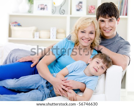 Portrait of happy cheerful family with little son with toothy smile - indoors - stock photo