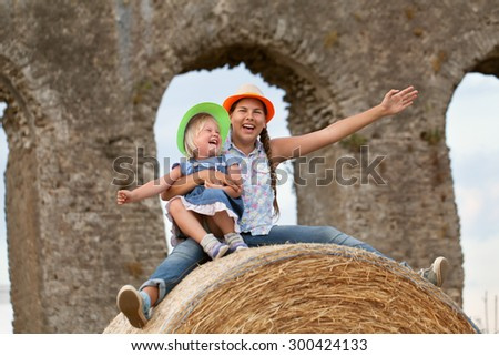 Portrait of happy cheerful sisters sitting on haystack on background of old aqueduct (ruins), outdoor - stock photo