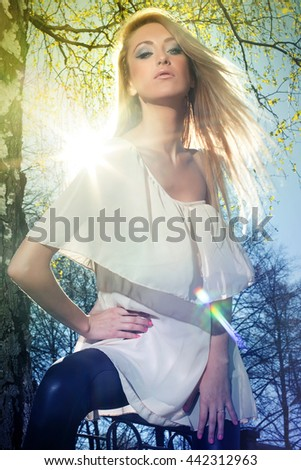 Portrait of happy cheerful young beautiful blond woman outdoors behind blue sun sky and tree.  - stock photo