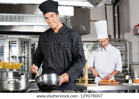 Portrait of happy chef cooking food with colleague chopping carrot in background - stock photo
