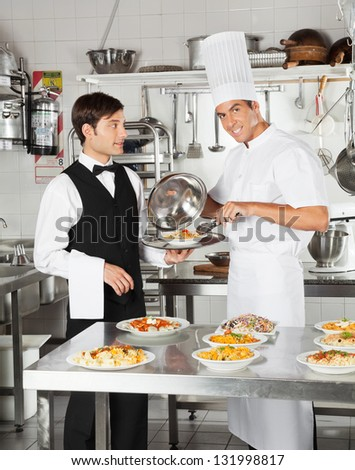 Portrait of happy chef giving pasta dish to waiter in restaurant kitchen - stock photo