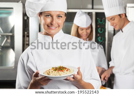 Portrait of happy chef presenting dish with colleagues in background - stock photo