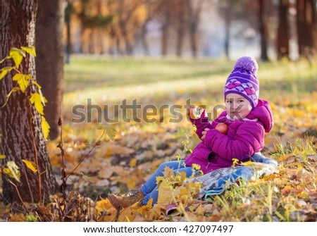 Portrait of happy child eating red apple outdoors in autumn - stock photo