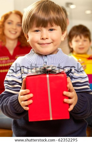 Portrait of happy child holding red gift box - stock photo