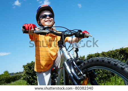 Portrait of happy child on bicycle against blue sky - stock photo