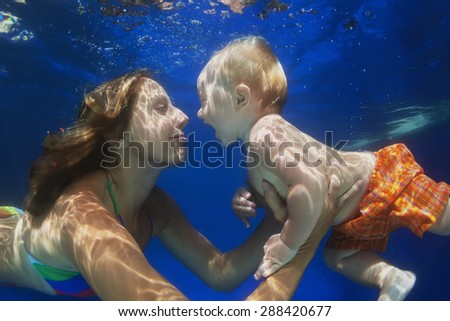 Portrait of happy child swimming underwater with fun in pool with diving positive mother Healthy lifestyle, active parents, and people water sports activity during summer family vacation with baby boy - stock photo