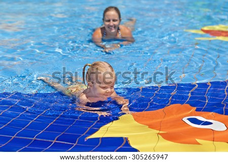 Portrait of happy child swimming with fun in blue outdoor pool with positive mother. Healthy lifestyle, active parents, and people water sports activity on summer family vacation with baby. - stock photo