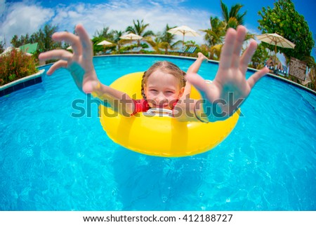 Portrait of happy child with inflatable rubber circle having fun in swimming pool - stock photo