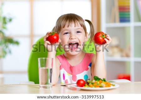 Portrait of happy child with vegetables sitting at table - stock photo