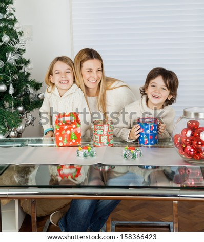Portrait of happy children and mother with Christmas presents at home - stock photo