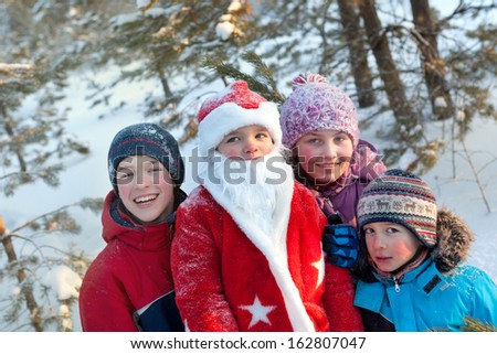 Portrait of happy children and Santa in winter forest - stock photo