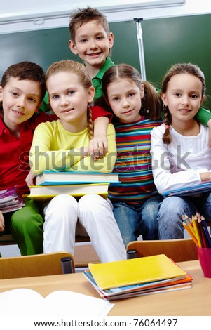 Portrait of happy children looking at camera in class - stock photo