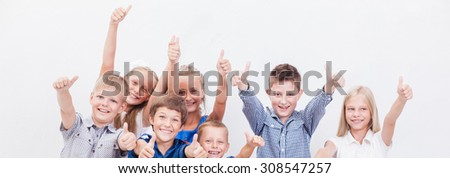 Portrait of happy children showing thumbs up gesture,  over white background - stock photo