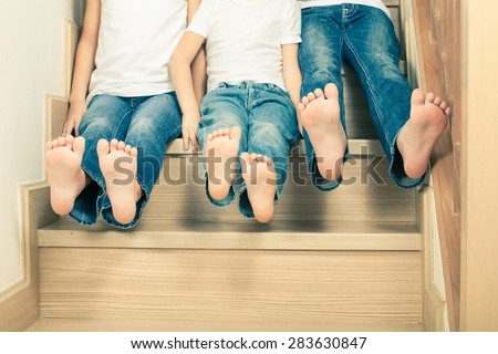 Portrait of happy children which are sitting on the stairs in the house. The concept of a brother and sister forever. - stock photo