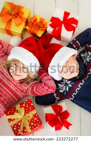 Portrait of happy children with Christmas gift boxes. Two kids having fun at home. Winter holidays concept. High angle view portrait - stock photo