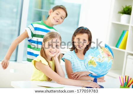 Portrait of happy classmates at workplace looking at camera in classroom - stock photo
