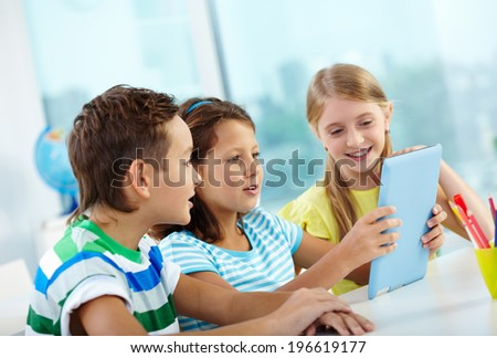 Portrait of happy classmates at workplace using digital tablet - stock photo