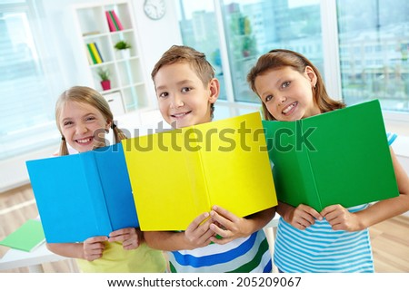 Portrait of happy classmates with multi-colored open books smiling at camera in classroom - stock photo