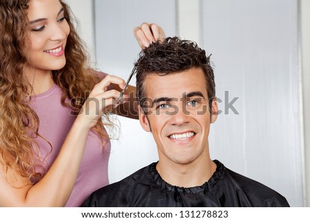 Portrait of happy client getting haircut from female hairdresser at salon - stock photo