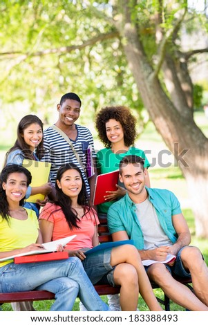 Portrait of happy college students studying on bench at campus - stock photo