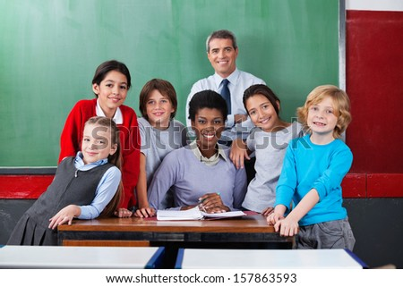 Portrait of happy confident male and female teachers with schoolchildren together at desk in classroom - stock photo