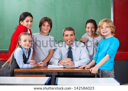 Portrait of happy confident mature male teacher with schoolchildren together at desk in classroom - stock photo