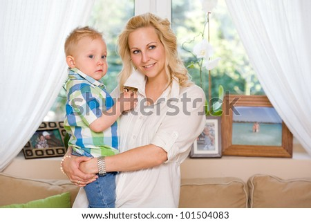 Portrait of happy confident young mother with her son at home. - stock photo