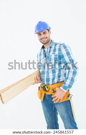 Portrait of happy construction worker holding wooden planks over white background - stock photo