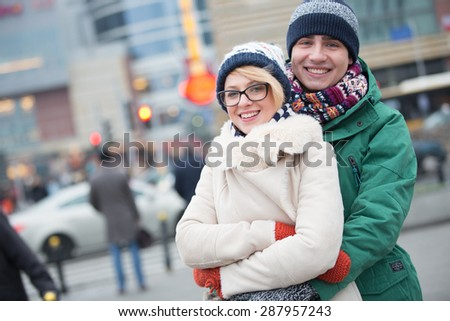 Portrait of happy couple embracing on city street during winter - stock photo