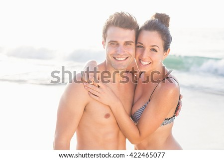 Portrait of happy couple embracing on the beach on a sunny day - stock photo