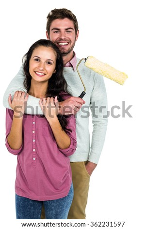Portrait of happy couple holding paint roller against white background - stock photo