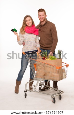Portrait of happy couple in full length with grocery shopping bags in shopping cart isolated on white background. - stock photo