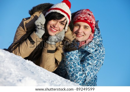 Portrait of happy couple in warm clothes looking at camera - stock photo