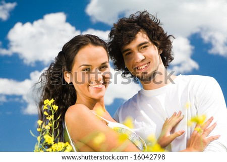 Portrait of happy couple looking at camera outside - stock photo