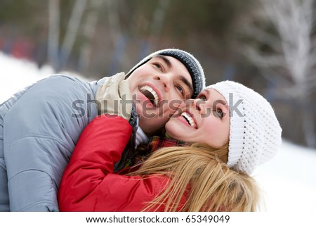 Portrait of happy couple looking upwards and laughing - stock photo