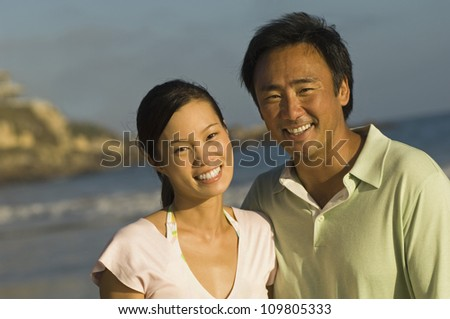 Portrait of happy couple on beach vacation - stock photo