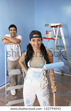 Portrait of happy couple painting blue color on wall - stock photo