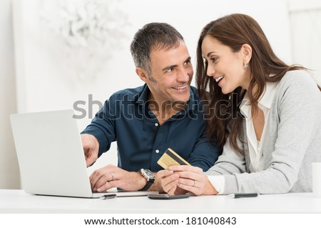 Portrait Of Happy Couple Shopping Online Using Laptop And Credit Card - stock photo