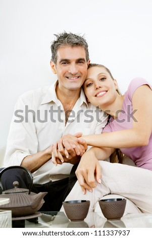 Portrait of happy couple sitting together while holding hands - stock photo