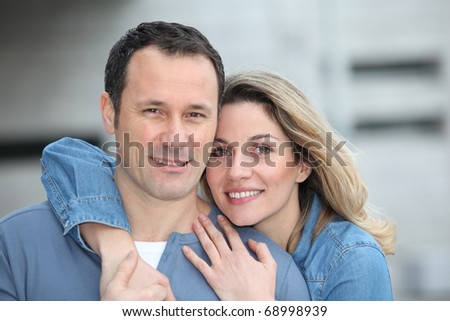 Portrait of happy couple standing outdoors - stock photo